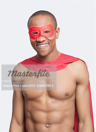 Portrait of young shirtless man in superhero costume smiling against gray background Stock Photo - Premium Royalty-Free, Image code: 693-06667802