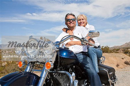 Senior couple on desert road sitting on motorcycle looking at camera Stock Photo - Premium Royalty-Free, Image code: 693-06667816