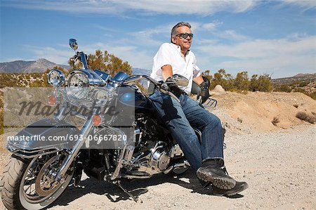 Senior man leaning on motorcycle on desert road Stock Photo - Premium Royalty-Free, Image code: 693-06667820