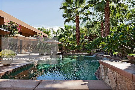 Luxury Villa with waterfall feature and palm trees Stock Photo - Premium Royalty-Free, Image code: 693-06667950