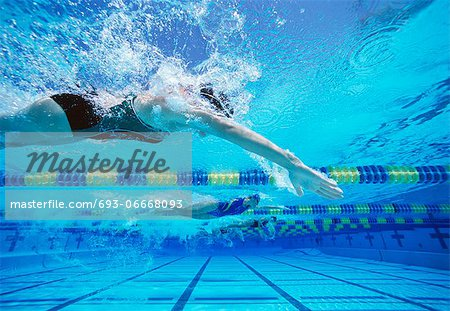 Four female swimmers racing together in swimming pool Stock Photo - Premium Royalty-Free, Image code: 693-06668093