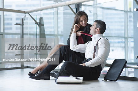 Businesswoman pulls male coworker towards her with his tie Stock Photo - Premium Royalty-Free, Image code: 693-06967348