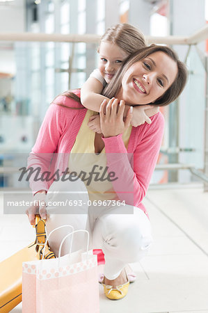 Young daughter hugs mother in shopping mall Stock Photo - Premium Royalty-Free, Image code: 693-06967364