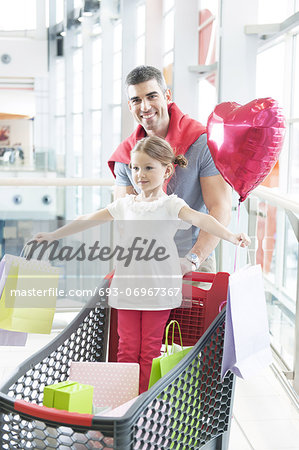 Father pushing young daughter in shopping trolley with shopping bags Stock Photo - Premium Royalty-Free, Image code: 693-06967367