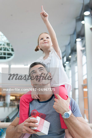 Young daughter points and sits on fathers shoulders Stock Photo - Premium Royalty-Free, Image code: 693-06967375