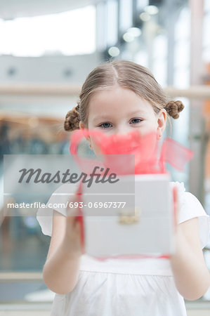 Young girl handing present towards camera Stock Photo - Premium Royalty-Free, Image code: 693-06967377