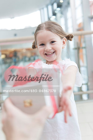 Young girl being giving a present Stock Photo - Premium Royalty-Free, Image code: 693-06967378
