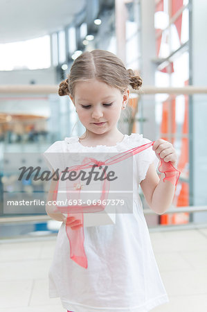 Young girl unwrapping ribbon on present Stock Photo - Premium Royalty-Free, Image code: 693-06967379