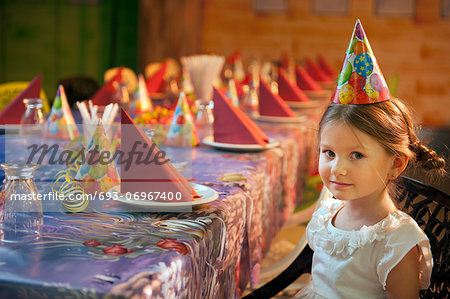 Young girl seated at her birthday table Stock Photo - Premium Royalty-Free, Image code: 693-06967400