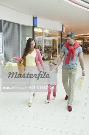 Young girl holding parents hands in shopping mall Stock Photo - Premium Royalty-Free, Image code: 693-06967406