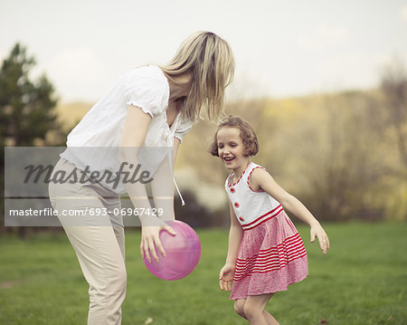 Mother and daughter playing with ball in the park Stock Photo - Premium Royalty-Free, Image code: 693-06967429