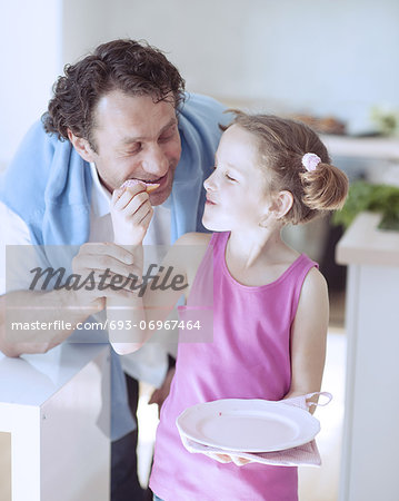 Young girl feeding her father Stock Photo - Premium Royalty-Free, Image code: 693-06967464