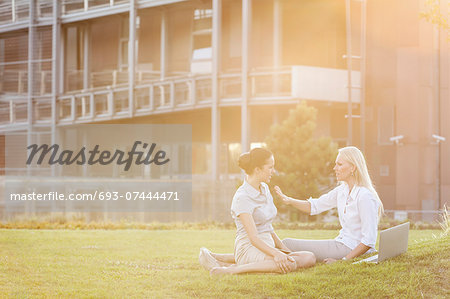 Young businesswomen discussing in office lawn Stock Photo - Premium Royalty-Free, Image code: 693-07444471