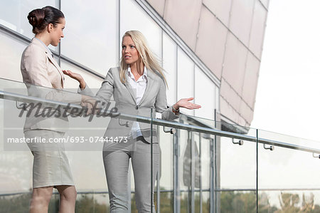 Young businesswoman arguing with female colleague at office balcony Stock Photo - Premium Royalty-Free, Image code: 693-07444473