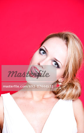 Caucasian woman wearing white dress on red background licking her lips Stock Photo - Premium Royalty-Free, Image code: 693-07444532
