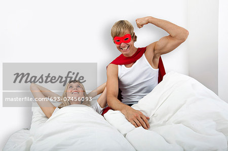Portrait of man in superhero costume with woman on bed Stock Photo - Premium Royalty-Free, Image code: 693-07456093