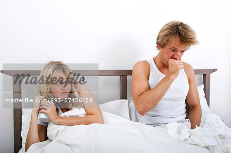 Scared woman looking at man coughing in bed Stock Photo - Premium Royalty-Free, Image code: 693-07456108