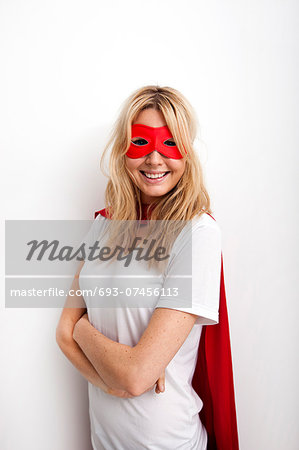 Portrait of confident woman in superhero costume against white background Stock Photo - Premium Royalty-Free, Image code: 693-07456113