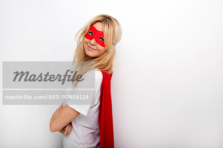Side view portrait of confident woman in superhero against white background Stock Photo - Premium Royalty-Free, Image code: 693-07456114
