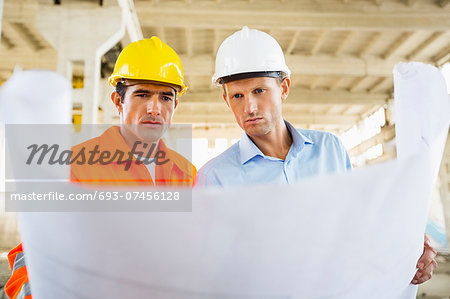 Male architects reviewing blueprint at construction site Stock Photo - Premium Royalty-Free, Image code: 693-07456128
