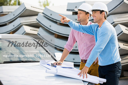 Architects with blueprints on car discussing at site Stock Photo - Premium Royalty-Free, Image code: 693-07456138