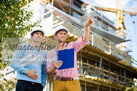 Male architects with blueprint and clipboard working at site Stock Photo - Premium Royalty-Free, Image code: 693-07456149