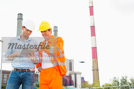 Two construction workers discussing over tablet PC at industry Stock Photo - Premium Royalty-Free, Image code: 693-07456182