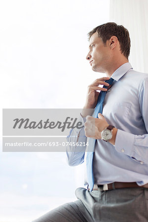 Thoughtful businessman adjusting necktie in hotel Stock Photo - Premium Royalty-Free, Image code: 693-07456214