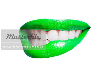 Close-up of teeth biting green lip over white background Stock Photo - Premium Royalty-Free, Image code: 693-07456328