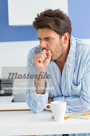 Young man coughing with coffee mug and medicine on kitchen counter Stock Photo - Premium Royalty-Free, Image code: 693-07456340
