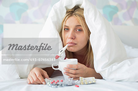 Portrait of sad woman with coffee mug taking temperature while wrapped in quilt on bed Stock Photo - Premium Royalty-Free, Image code: 693-07456383