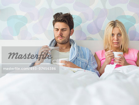Sad couple holding coffee mugs while relaxing on bed Stock Photo - Premium Royalty-Free, Image code: 693-07456386