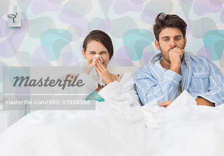 Young couple suffering from cold and flu in bed at home Stock Photo - Premium Royalty-Free, Image code: 693-07456388