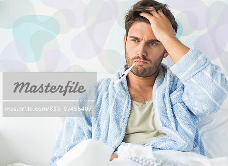 Sick man with thermometer in mouth sitting on bed at home Stock Photo - Premium Royalty-Free, Image code: 693-07456407