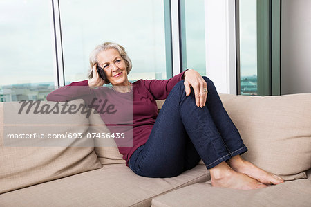 Full-length of senior woman answering smart phone on sofa at home Stock Photo - Premium Royalty-Free, Image code: 693-07456439