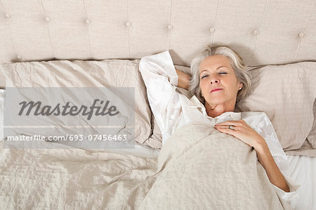 Senior woman sleeping in bed Stock Photo - Premium Royalty-Free, Image code: 693-07456463