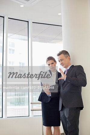 Businessman using digital tablet with female colleague in office Stock Photo - Premium Royalty-Free, Image code: 693-07542148