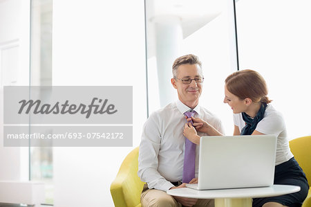 Businesswoman putting on tie to male colleague at lobby Stock Photo - Premium Royalty-Free, Image code: 693-07542172