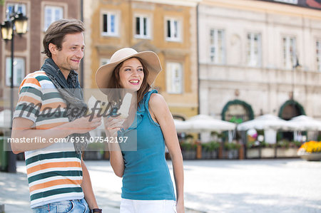 Tourist couple enjoying ice cream cones during vacation Stock Photo - Premium Royalty-Free, Image code: 693-07542197
