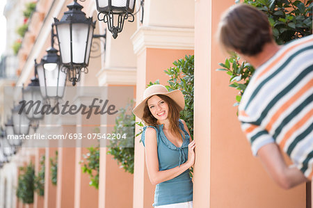 Happy woman playing hide-and-seek with man amongst pillars Stock Photo - Premium Royalty-Free, Image code: 693-07542204