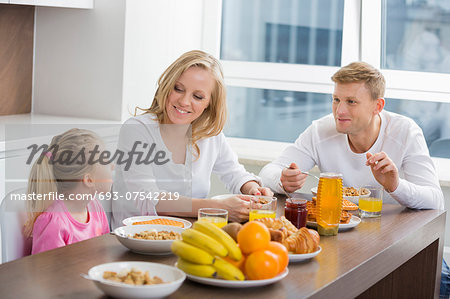Happy family of three having breakfast at table Stock Photo - Premium Royalty-Free, Image code: 693-07542219