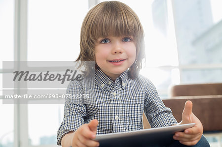 Portrait of cute boy holding tablet computer at home Stock Photo - Premium Royalty-Free, Image code: 693-07542235