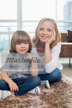 Portrait of happy mother sitting with boy on rug in living room Stock Photo - Premium Royalty-Free, Image code: 693-07542236