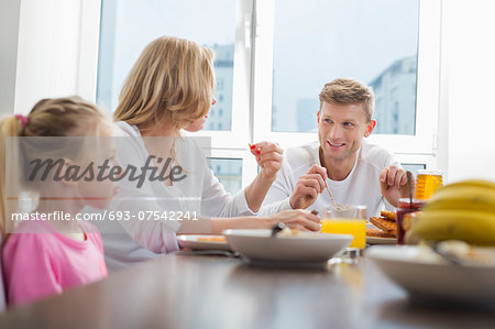Happy family of three having breakfast at table Stock Photo - Premium Royalty-Free, Image code: 693-07542241