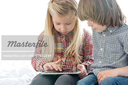 Brother and sister using tablet PC in bedroom Stock Photo - Premium Royalty-Free, Image code: 693-07542249