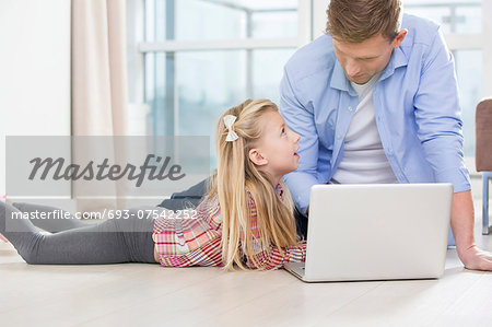 Father and daughter using laptop on floor in living room Stock Photo - Premium Royalty-Free, Image code: 693-07542252