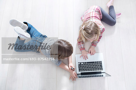 High angle view of brother and sister using laptop on floor at home Stock Photo - Premium Royalty-Free, Image code: 693-07542256