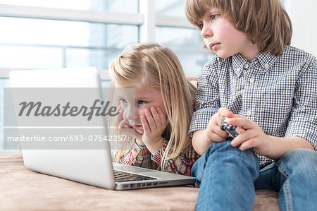 Brother and sister looking at laptop in living room Stock Photo - Premium Royalty-Free, Image code: 693-07542257