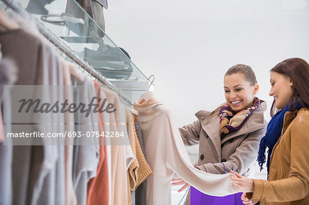 Happy friends choosing sweater in store Stock Photo - Premium Royalty-Free, Image code: 693-07542284