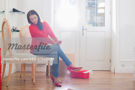 Full length of woman trying on footwear in store Stock Photo - Premium Royalty-Free, Image code: 693-07542299